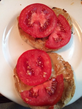 Fresh tomatoes, butter and peanut butter on a toasted English Muffin