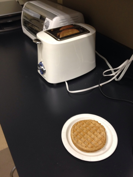 A coworker's waffle waits in line as the previous person's toast gets cold.