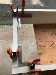 90° clamping aids are readily available. They hold things in place until I'm ready to glue and screw things into place.