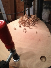 The stool seat is pinned at an angle as I drill the mortises.
