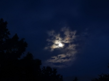 Full moon breaking out from the clouds