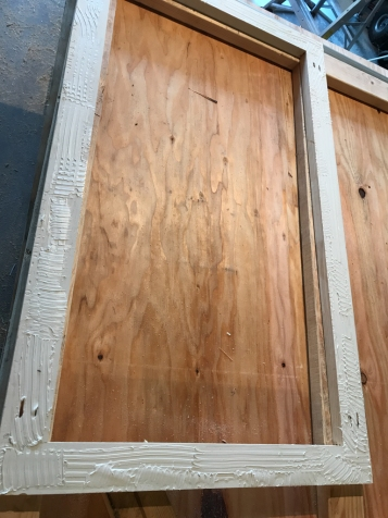 The frame is covered with exterior plywood, which is glued and stapled to the frame.