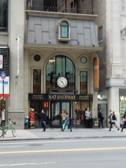 I like how this little building is sandwiched in between two much taller buildings. And I like the clock.