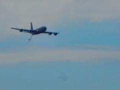 KC-135 aerial refueling plane making a pass with the fueling boom extended.