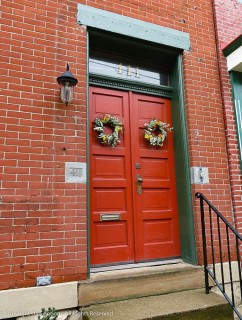 Red doors. Wreaths. Lamp. Brick work. This has everything.