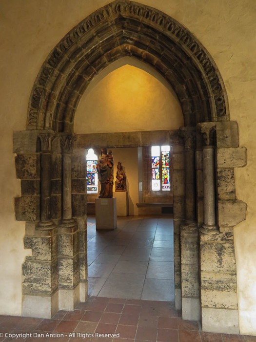 This doorway arch is set in contrast to a much simpler one as an example of the difference in design from the 13th to the 15th century.