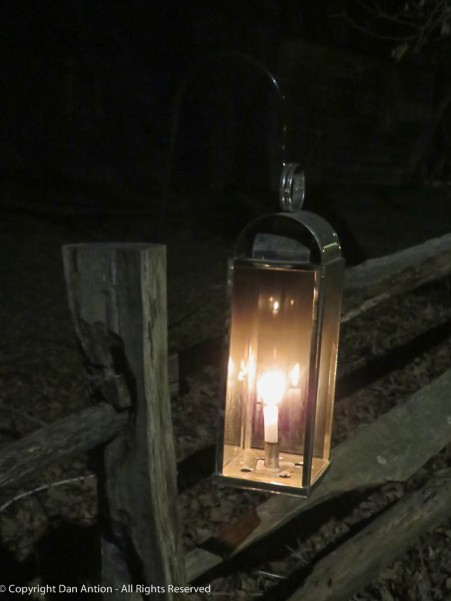 Candles on fenceposts light the path.