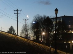 Looking up from Great River Park at the building at the top of the levee and the moon.