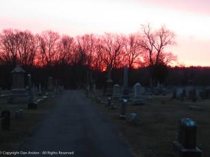 The sun is rising behind Elm Grove Cemetery