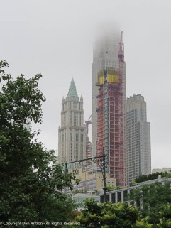 The fog obscures the top of the building, but I can see the crane.