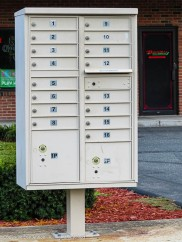 I worked three summers for the Post Office. All of those little doors are part of one large door. The mailman opens the large door, fills the slots behind the little doors and locks it back up.
