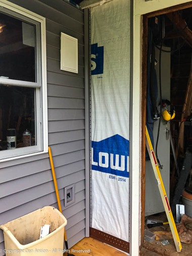 Once the door was moved out from the wall, there was room to install the siding. It starts with a wrap, a starter strip and some J-channel.