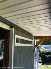 The soffit fits between the barn door rail and the original soffit.