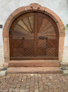 The door on the right includes the center stile. I'm guessing that the left hand door includes a similar feature and that they overlap. If you look closely, you can see an angled cut in the base rail indicating where the doors meet.