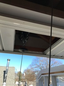 The hoist is just inside the garage. An anchor point for the cable is concealed in the soffit.