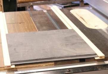 Slate, mated to the wooden frame. The base provides support and necessary glue surface to hold the frame together.