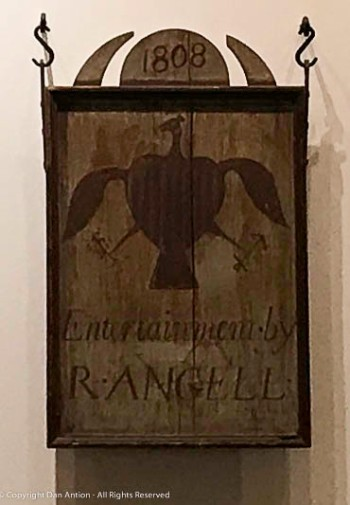 From CHS records - the eagle was a common motif in tavern signs, this one has a most unusual appearance, with its limp wings, scrawny feet, and heart-shaped body. The nine white and eight red stripes symbolize each of the seventeen states in the Union at the time and allude to the national seal. However, the eagle grasps not the usual arrows and olive branch, but rather a laurel branch and an anchor, the central image of the Rhode Island state seal.