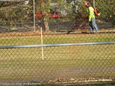 Cleaning the warning track. The crows appreciate that, they hit a long ball.
