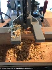 A mortising machine cuts a square hole. The drill inside removes most of the wood. The chisel cleans up the edges. A little elbow grease is required.