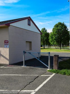 A door and a gate. The roll-up door in the side of the building has been used for concessions. The gate is to prevent vehicles on the path.