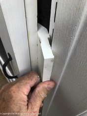 I had to build out a block on which to install the door latch. The first layer has to sneak behind the trim and over the nailing flange of the corner board.