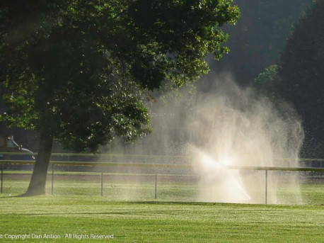 It was a windy day and the sprinkler hit the safety padding on the top of the fence.