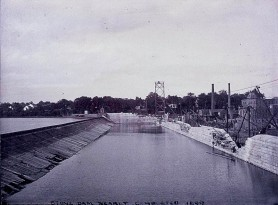 A cross section photograph of the Holyoke Dam during the third and present structures construction in the late 1890s, showing the combined inner masonry and outer granite cap. The tower in the background is one of two belonging to once the largest cableway in the world, used for transporting some materials along the height of the structure, in tandem with the narrow gauge rail (seen left) and several cranes. circa 1898 Source Canal Park Committee Records, South Hadley Public Library - Creative Commons license.
