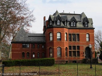 Dormers, details in the brickwork, interesting windows, and an arched entrance. Does it get any better?
