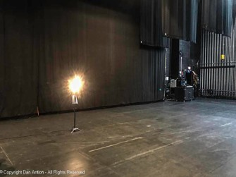 The ghost light. Left on at all times to a) prevent anyone from falling into the orchestra pit, or b) to prevent the theater ghosts from playing at night,