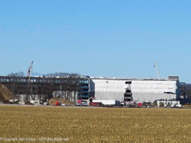The Amazon warehouse is being gradually clad in plain gray concrete panels.