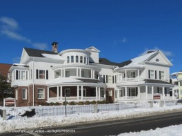 """Colonial Funeral Home. The Colonial Revival house stands out for its distinctive circular """"wedding cake"""" porches, which have Tuscan columns on the first level and Ionic columns on the second level."""