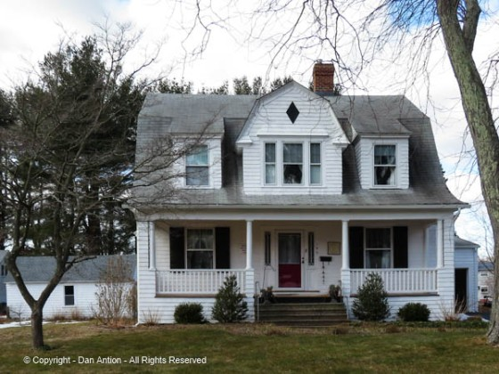 """As described in the NRHP form, """"A large gambrel dormer, flanked by smaller shed dormers, dominates the lower slope of the facade roof, which flares out over an open porch. Sometimes called Dutch Colonial Revival."""""""