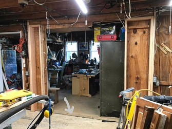 The wires have been tacked into place. That cabinet has been moved. Casters have been added to the workbench. The arrow is pointing to the problem. The two floors are at different heights. That's my next job.