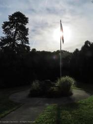 As the sun burns through the fog, it shines behind the flag.